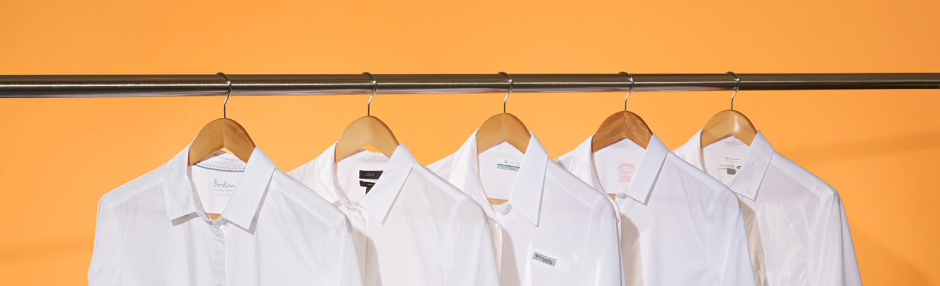image of five white shirts on hangers