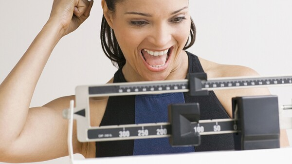 A woman smiling as she weighs herself on a scale