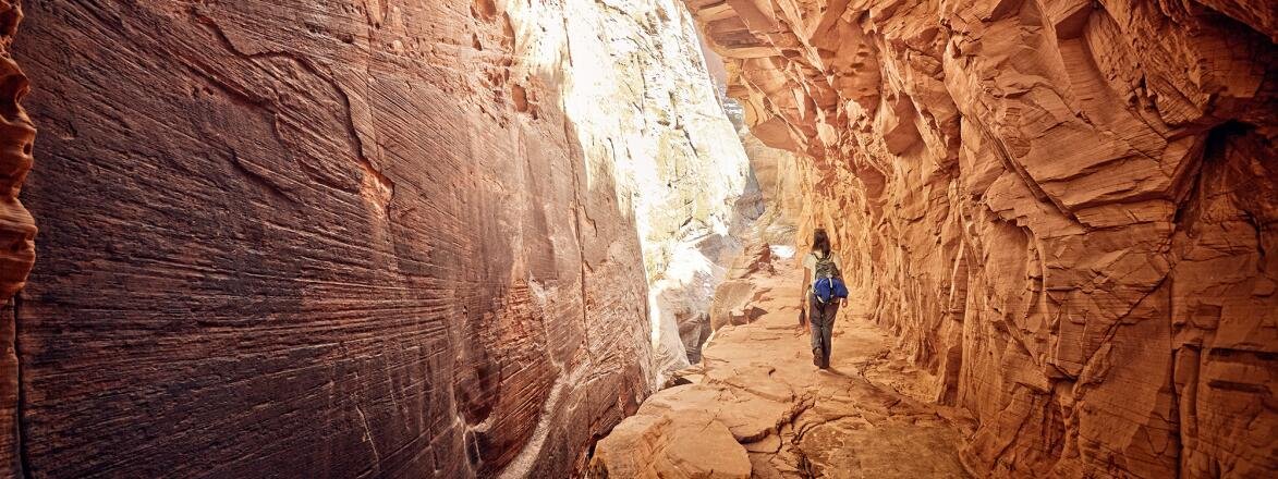 female hiker walking through a cave in Zion national park