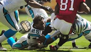 A professional football player loses his helmet during a play on the field