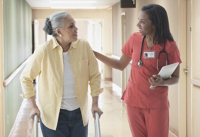 Older patient talking with nurse in hospital