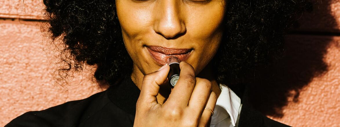 beautiful African American woman putting on lipstick