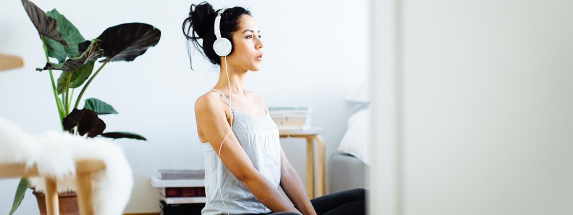 young woman practicing yoga with headphones on while using app on her phone
