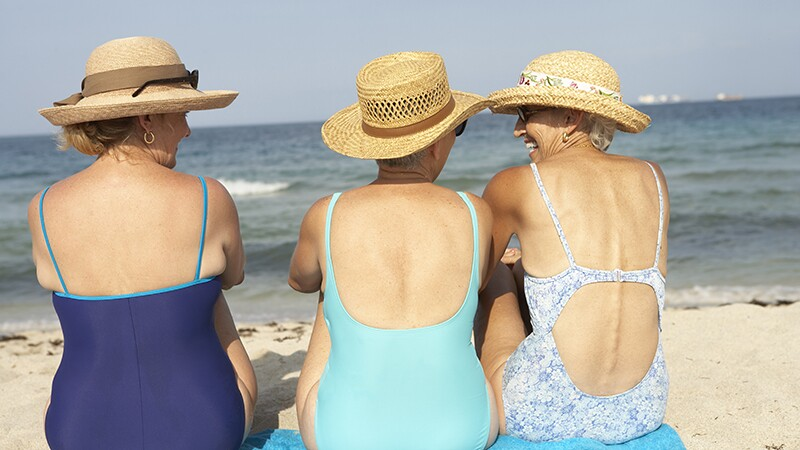 Three women sitting on the beach together