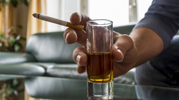 A close up of a hand holding a cigarette and shot glass
