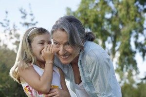 Girl Whispering In Grandmother's Ear