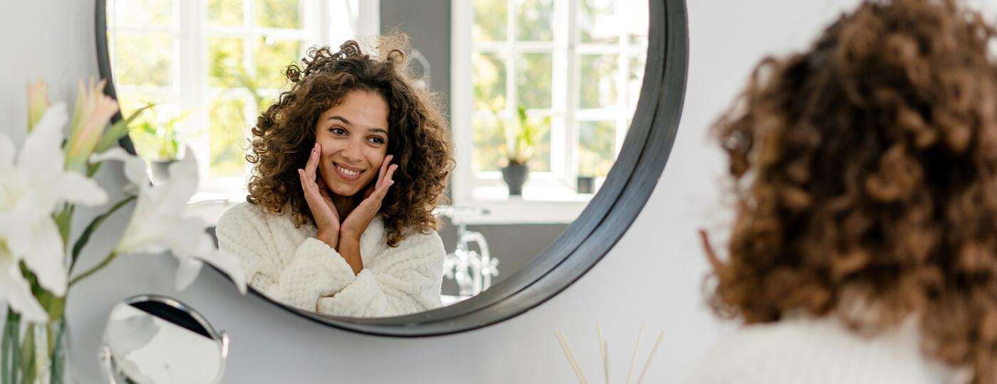 image_of_woman_happily_looking_in_mirror_GettyImages-1282976099_1800
