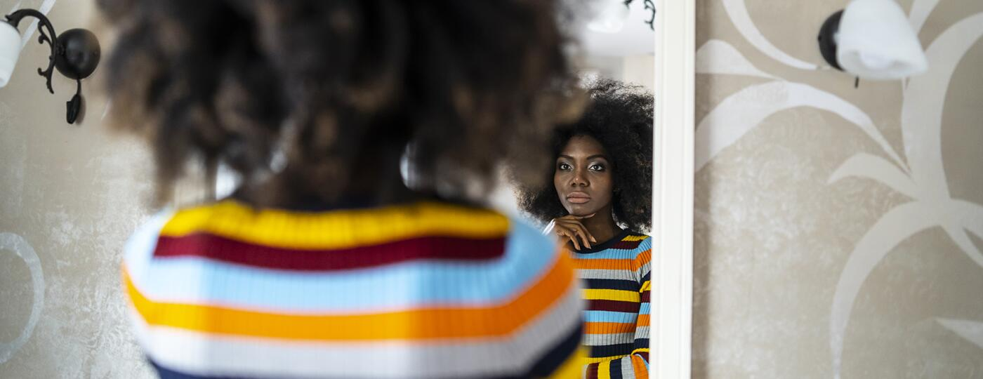 image_of_woman_looking_in_mirror_contemplative_GettyImages-1135286715_1800