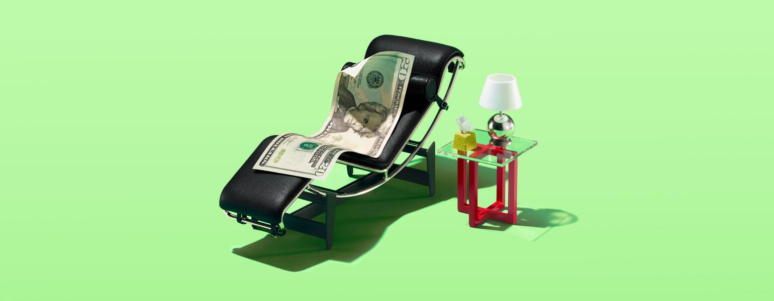 A 20 dollar bill sitting in a tiny therapist chair with a lamp and tissues