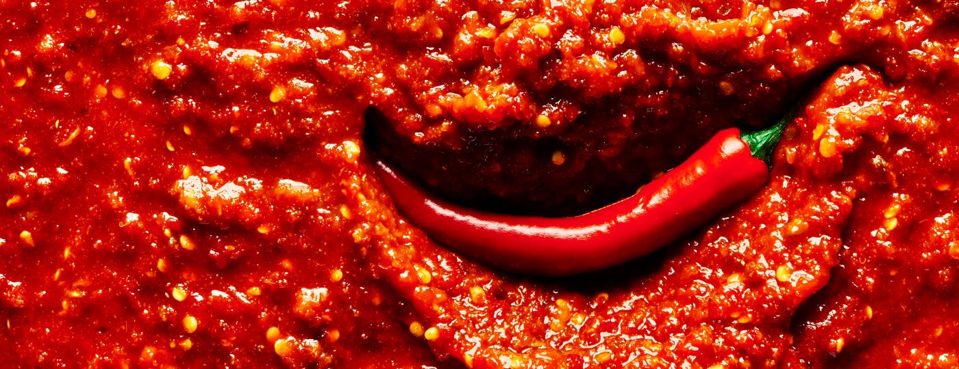 An image of a chili pepper in hot sauce.