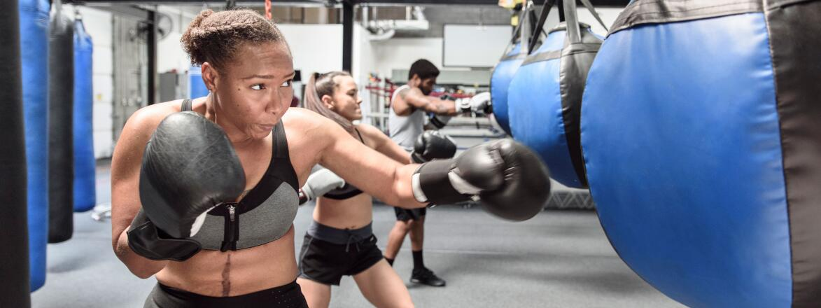 Woman hitting a blue punching bag with black boxing gloves
