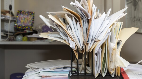 Messy, chaotic, file rack on a desk in cluttered room