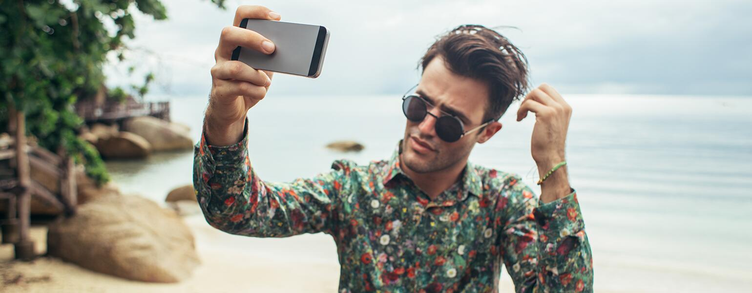Narcissistic man taking photo of himself on the beach with his phone.