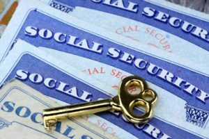 Gold key laying on social security card