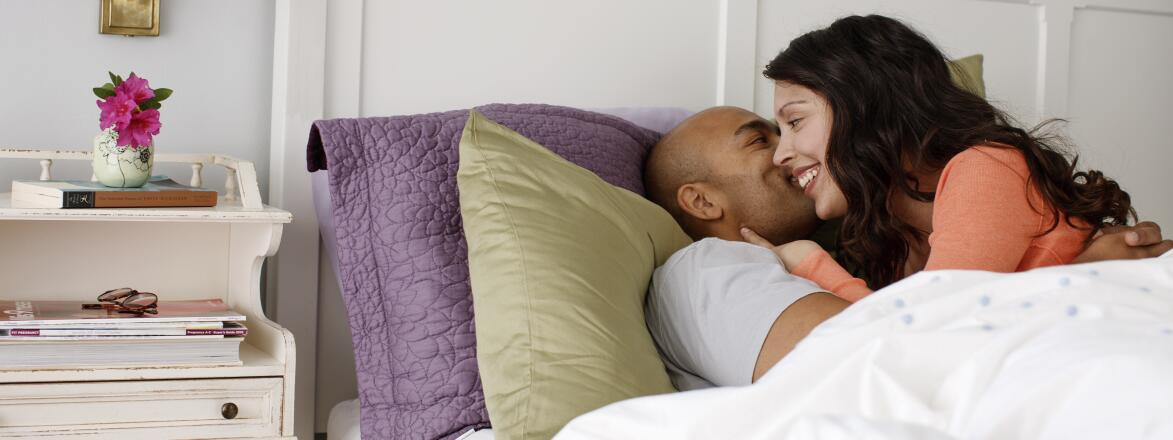 couple in bed whispering to each other