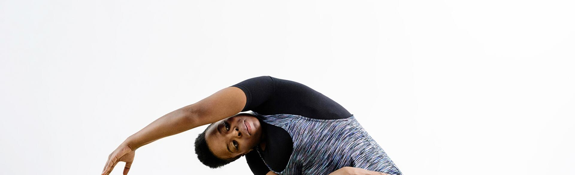 A photo of woman bent to her right side in a yoga pose, while sitting on a yoga mat.