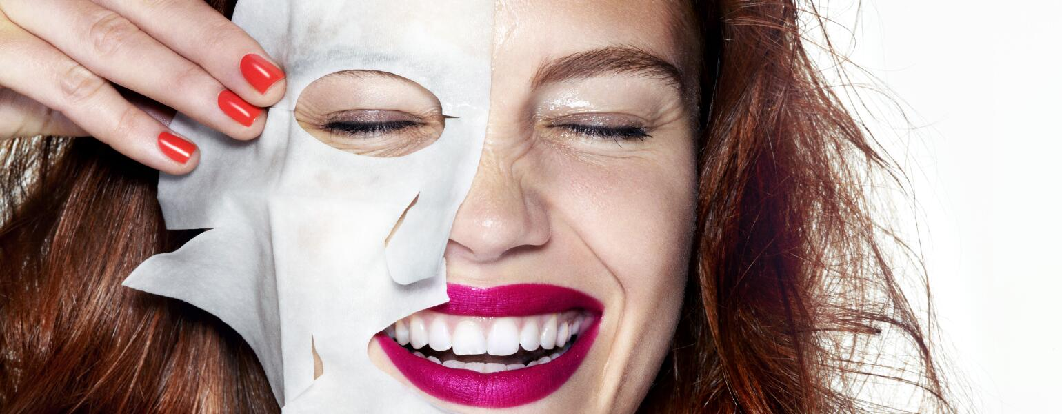 woman smiling with half of a sheet mask on her face