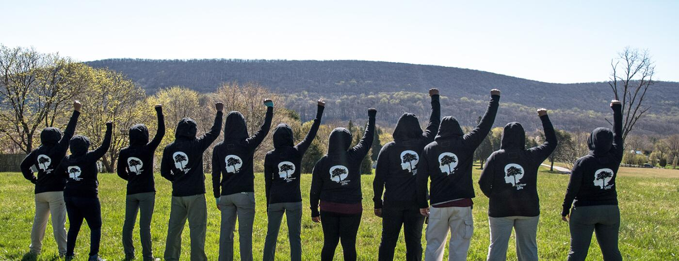 Black women hiking group empowering each other with fists in air outside.