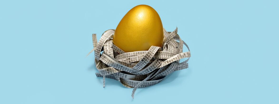 Golden egg in nest of strips of newspaper stock prices