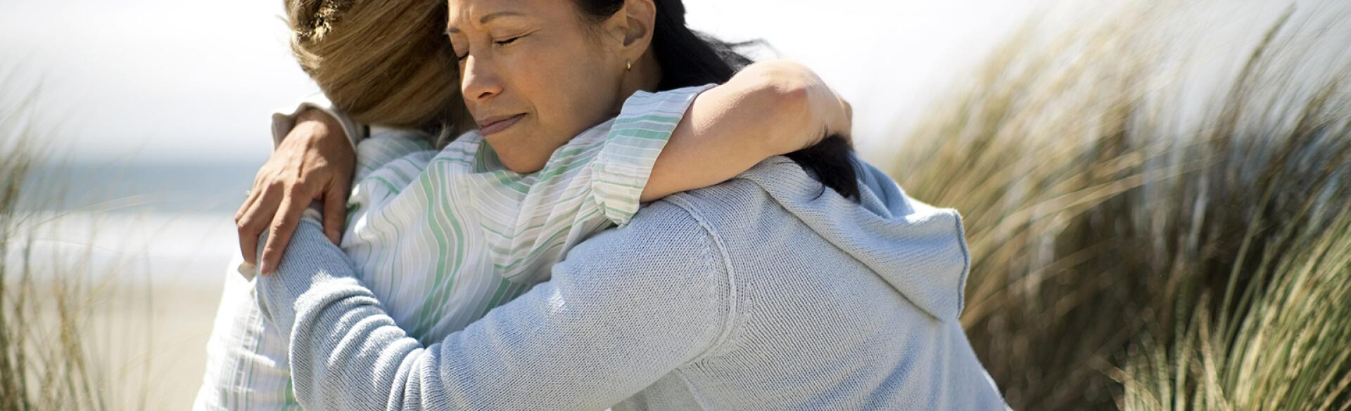 Friends hugging to mourn the loss of one of their parents.