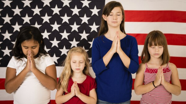 Multi-Ethnic Girls Praying in Front of American Flag