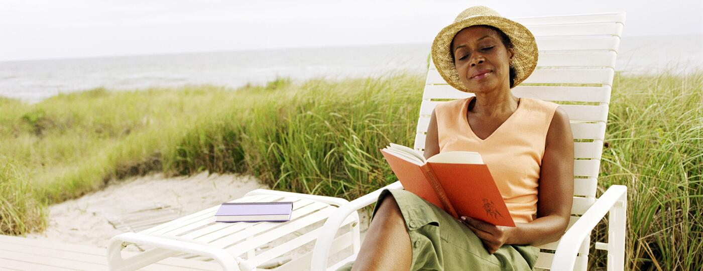 image_of_woman_reading_a_book_outside_on_beach_chair_GettyImages-200158560-001_1800