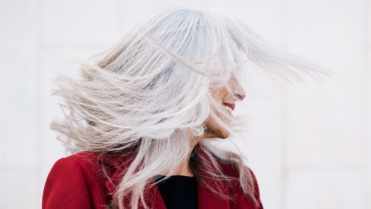 Portrait Of A Mature Woman With Grey Long Hair In Movement.
