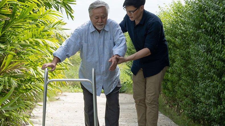 Man helps older man walk with walker