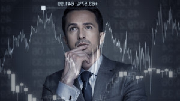 Man in suit and tie contemplating stock market charts