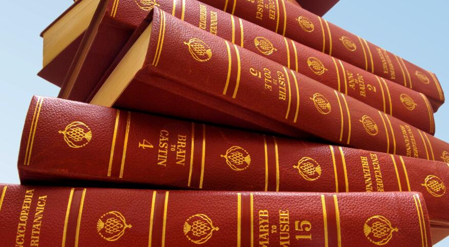 stack of encylopedia britanicas on a blue background