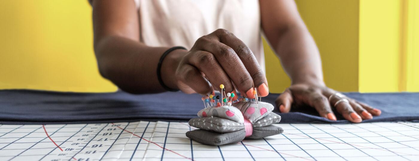 Woman Seamstress adjusting a garment on yellow background