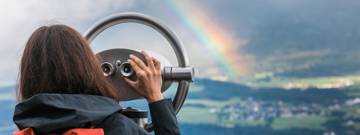 Woman looking through tower viewer at a rainbow