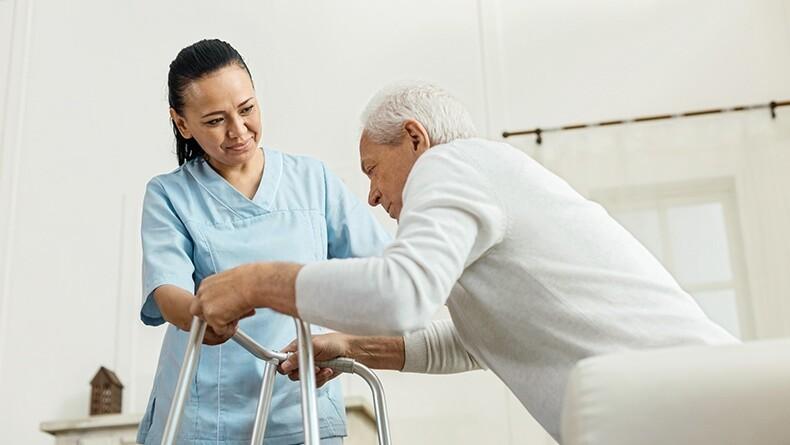 Nurse helping older man with a walker