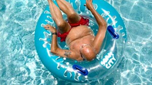Man lounges in a pool. Heat wave can be dangerous for boomers and seniors