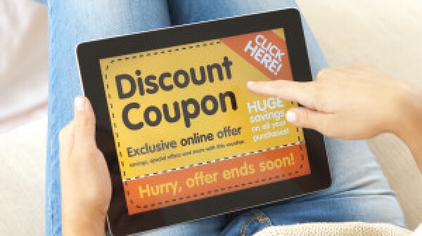 Woman using a discount coupon on a digital tablet on the sofa