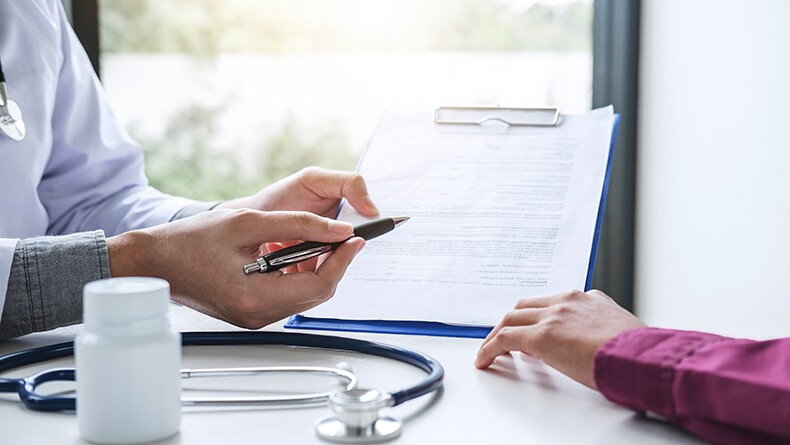Hands complete paperwork on a clipboard in a medical setting.