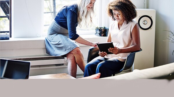 Two women discussing looking at a tablet together in an office
