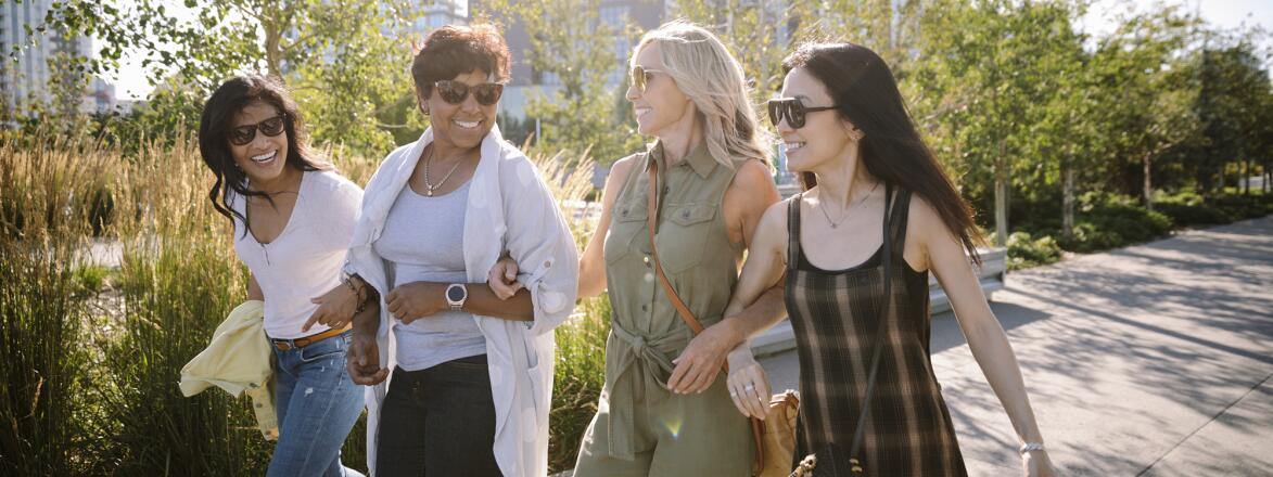 4 women walking down a sunny city sidewalk with linked arms
