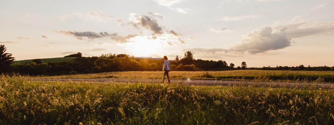 woman walking on a countryside road at dusk, finding the beauty in 2020