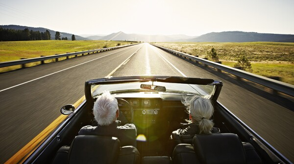 A man and woman driving in a convertible on an open road