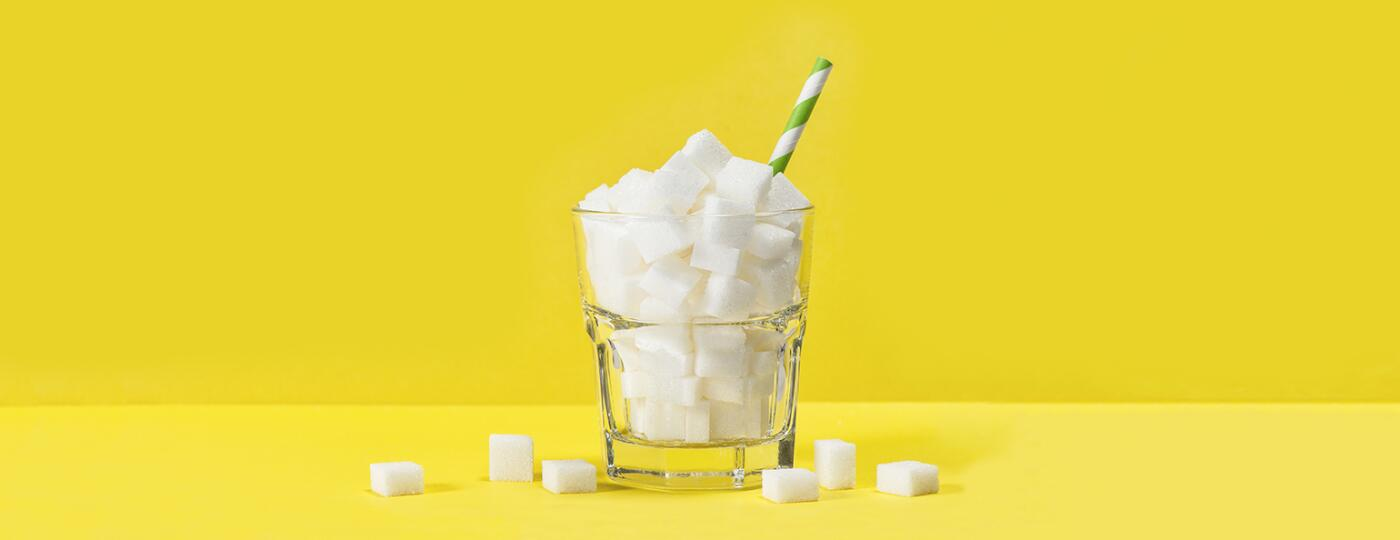 cup filled with sugar cubes with straw in it
