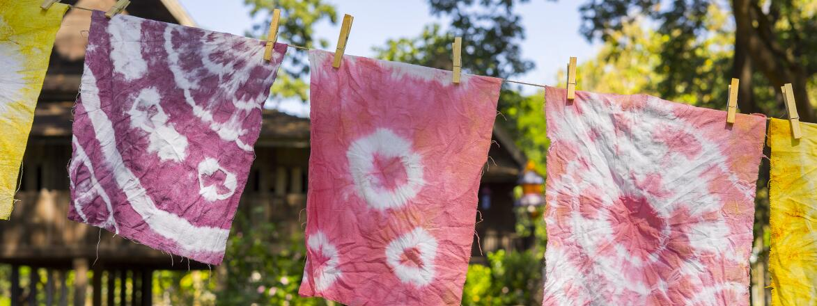 Colorful abstract tie dyed fabric hung up to dry on clothesline