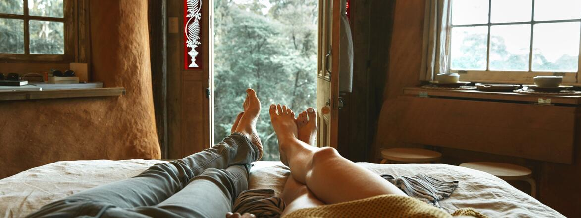 An image of a man and women's legs in bed, where they are lounging together and holding hands.
