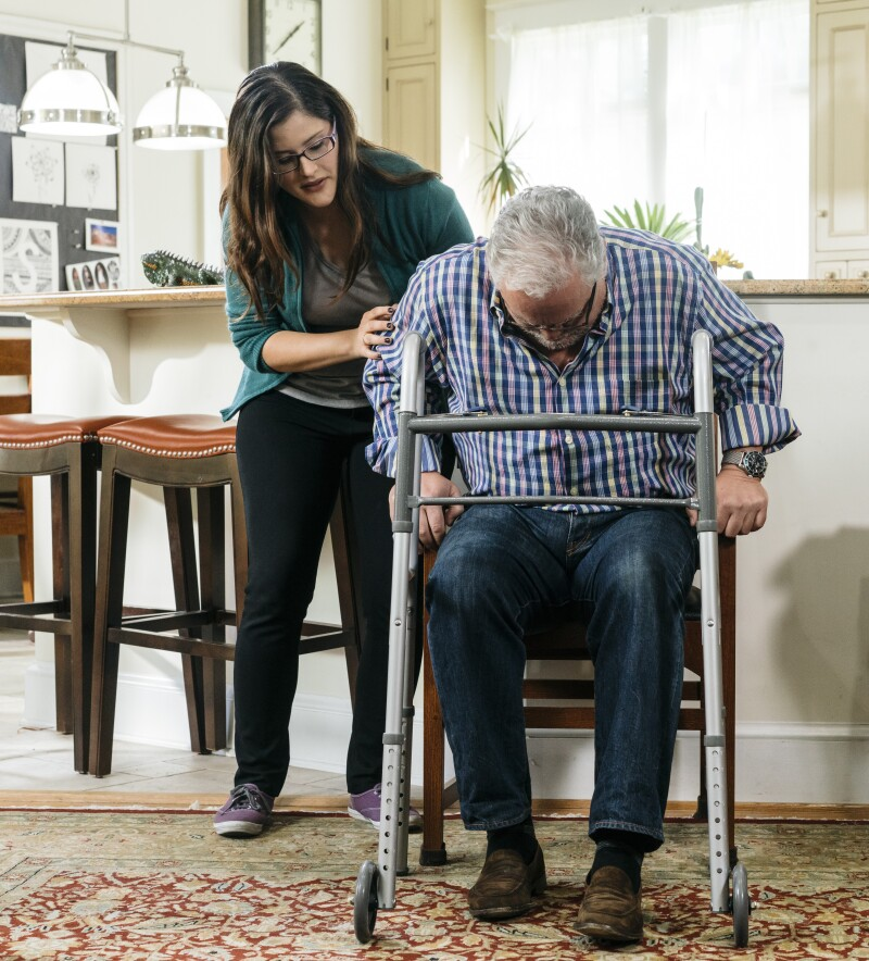 Young Hispanic woman helping her Hispanic father transfer from a seated to standing position using a walker as support.