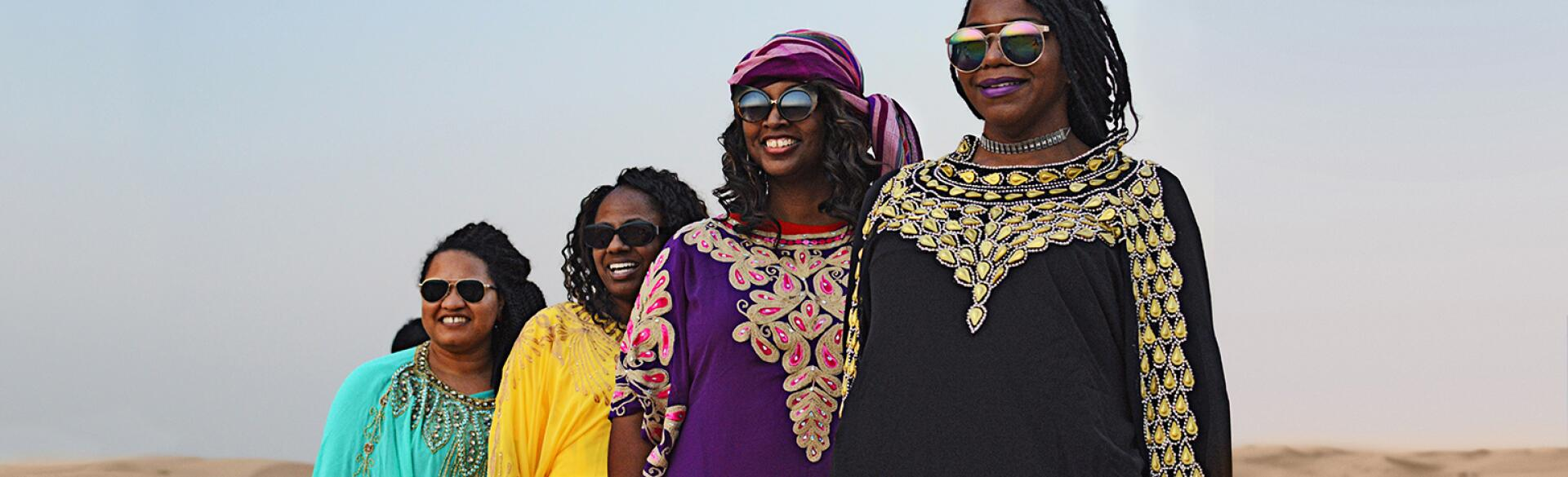 A group of four women stand in the UAE desert near Abu Dhabi.