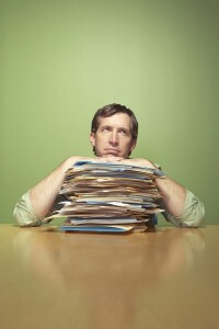 Man with piles of work