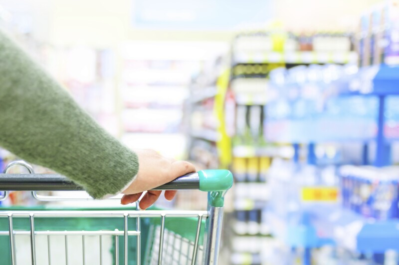 Close-up of woman pushing shopping trolley for grocery