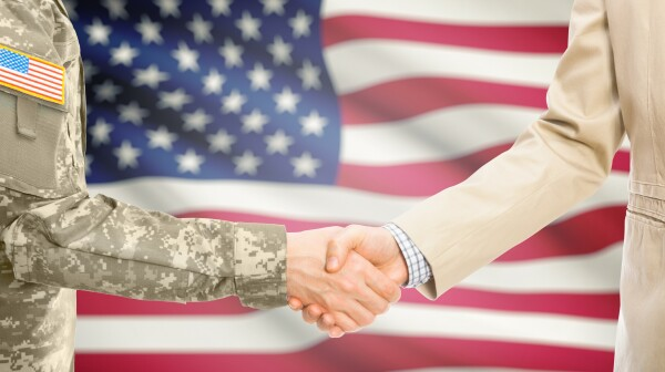 USA military man in uniform and civil man in suit shaking hands with national flag on background - United States
