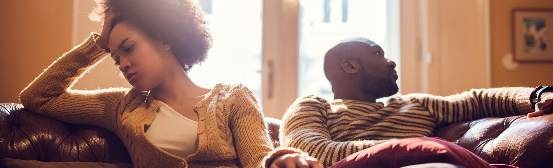 Black woman upset sitting on couch with husband after finding out he was cheating on her.
