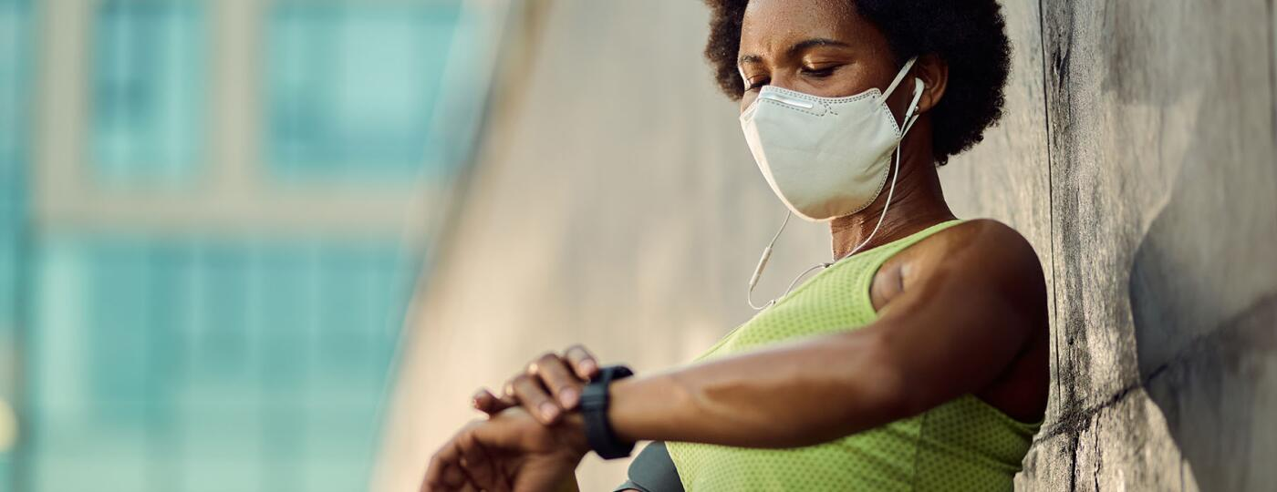 image_of_woman_wearing_mask_and_checking_watch_GettyImages-1256557417_1800.jpg